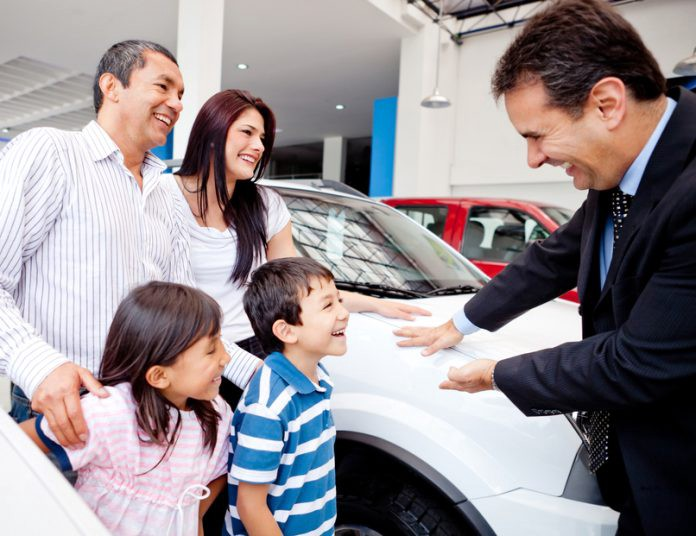 A salesperson addressing a family at a car showroom