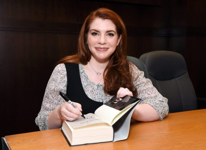 Author Stephenie Meyer sitting at a desk and signing a copy of her book.