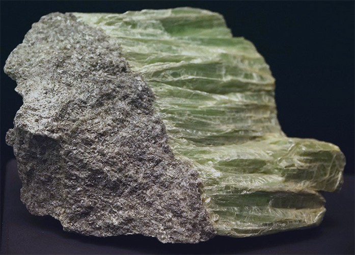 A rock composed of serpentine topped with pale green mineral crystals.