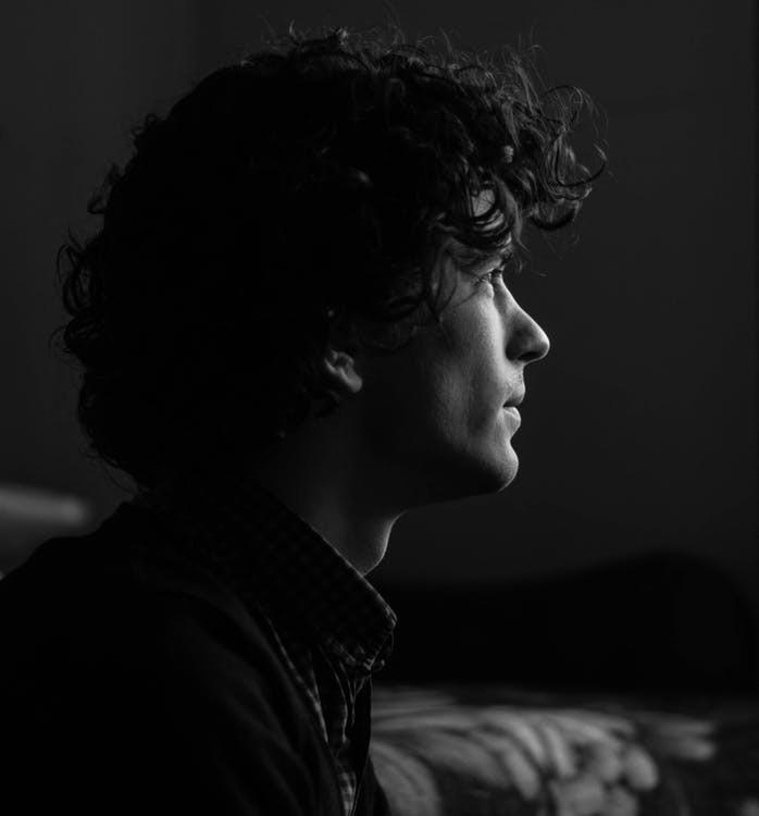 An image of a young man staring into space. It's black and white, so you know he's all sad and stuff.