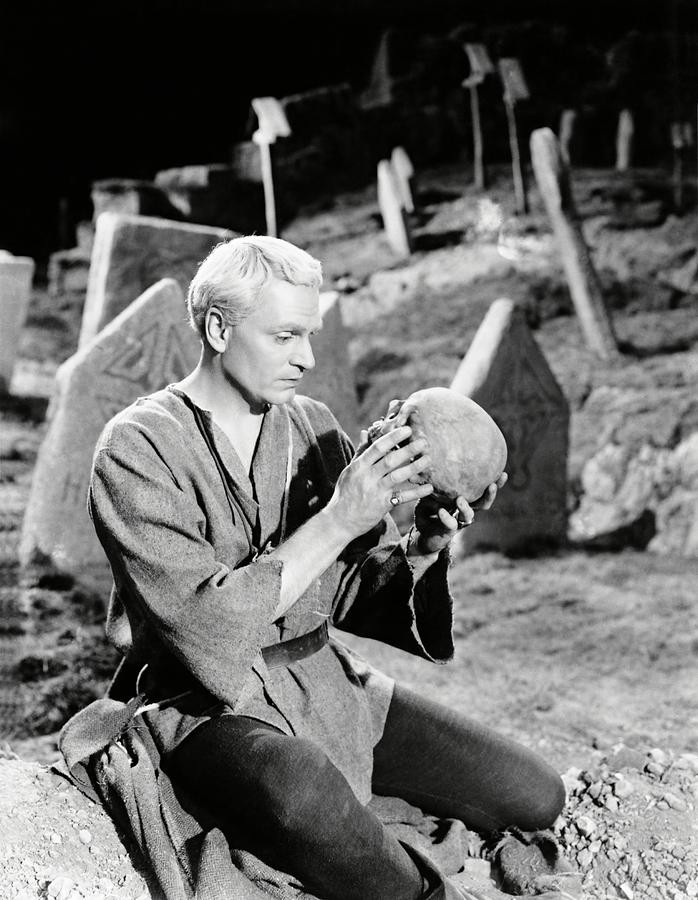A B&W photo of Laurence Olivier as Hamlet contemplating Yorick's skull.
