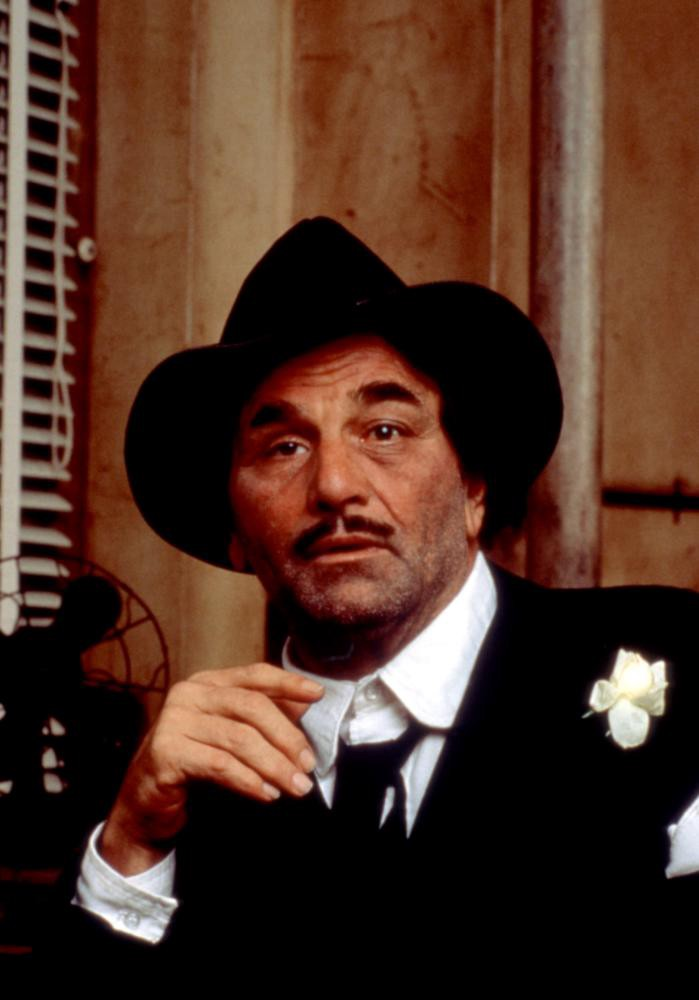 Peter Falk in a black suit, black hat and black tie with a white flower in his lapel.