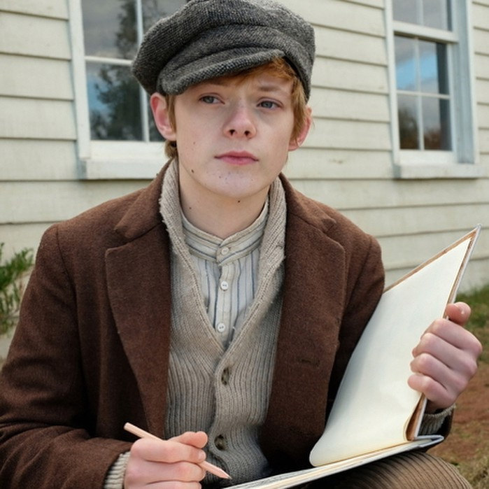 Cole, from the TV series 'Anne with an E', holds his sketchbook and looks up with a face that is used to hiding emotions.