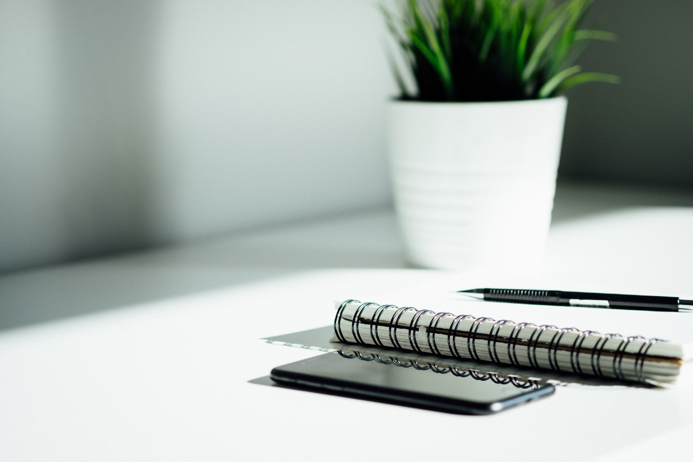 A stock photo. There is a smartphone sitting face-up on a desk beside a opened spiral coiled notebook. There is a black ballpoint pen resting on top of the notebook. In the background, there is a succulent in a white ceramic pot.