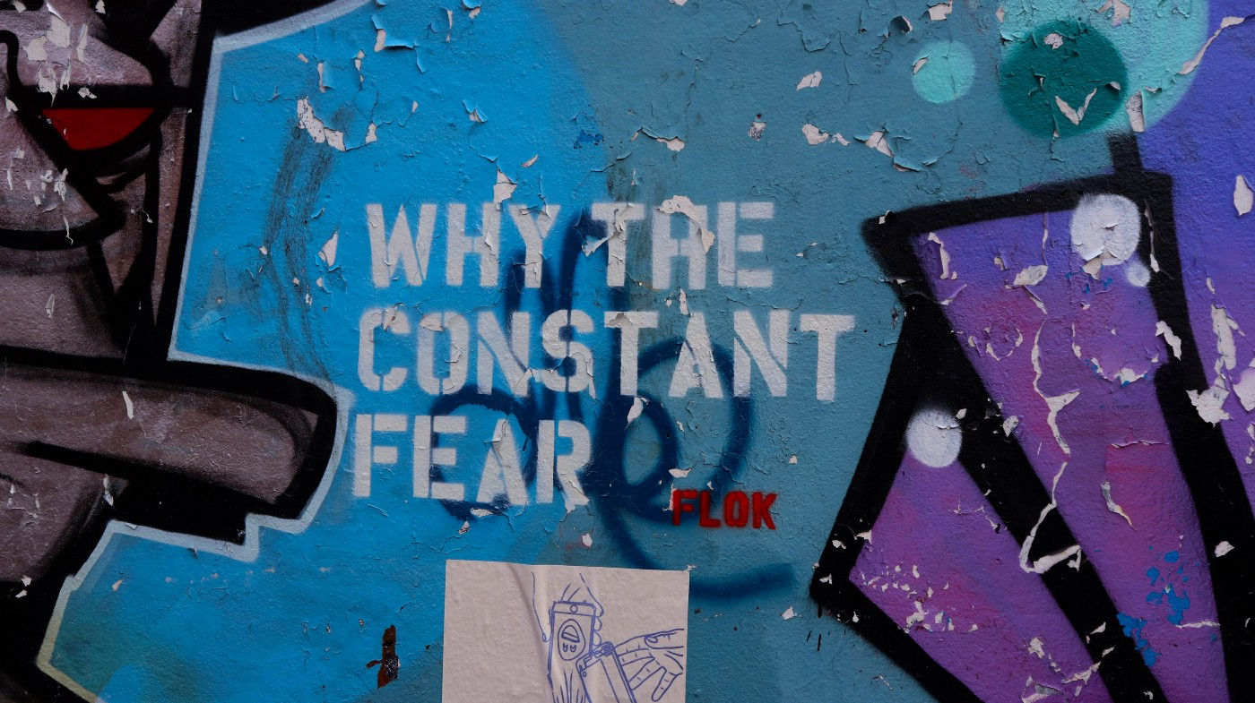 worn Graffiti  that says: Why the Constant Fear. Story: Fear Inventory by Rena Willis