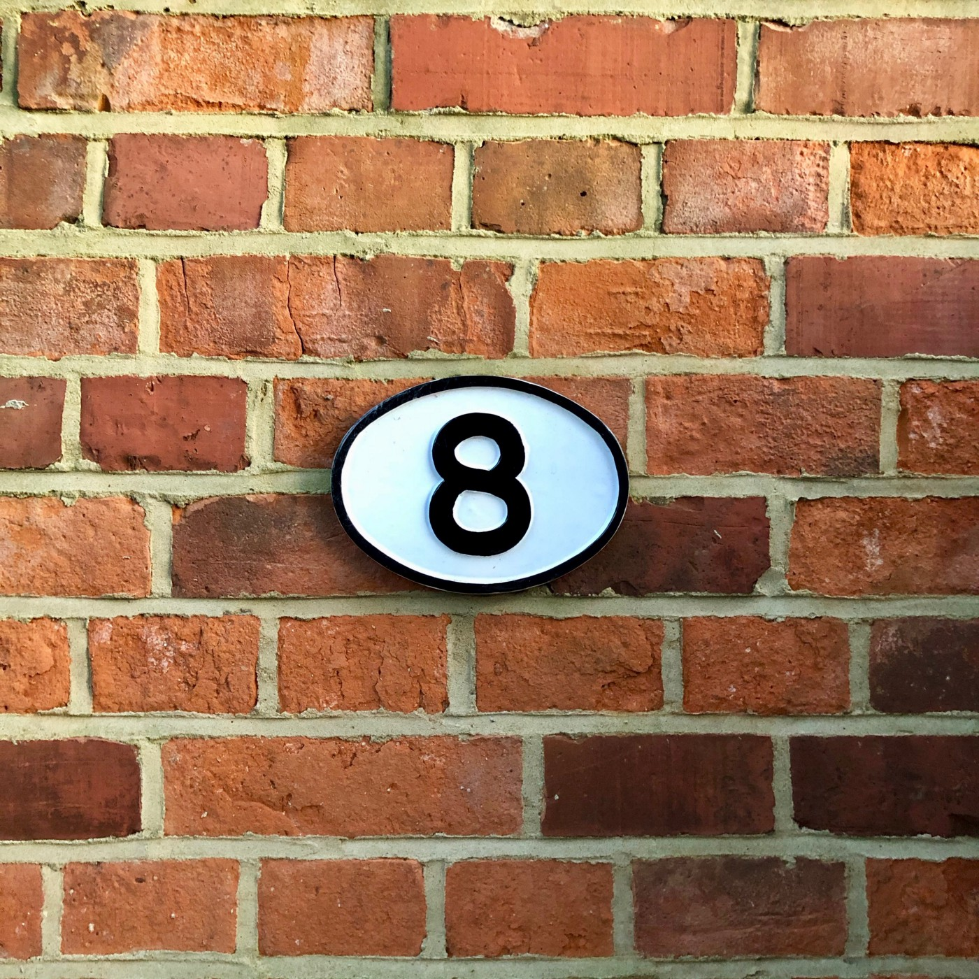 A sign with the number 8 is posted on the middle of a brick wall. The sign is oval in shape, and black and white in color. The bricks are red and brown.