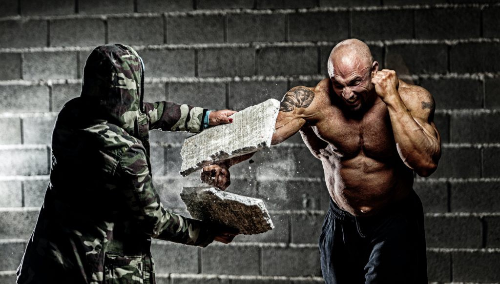 How to wire your brain for peak performance. Picture of a man punching through a stone block.