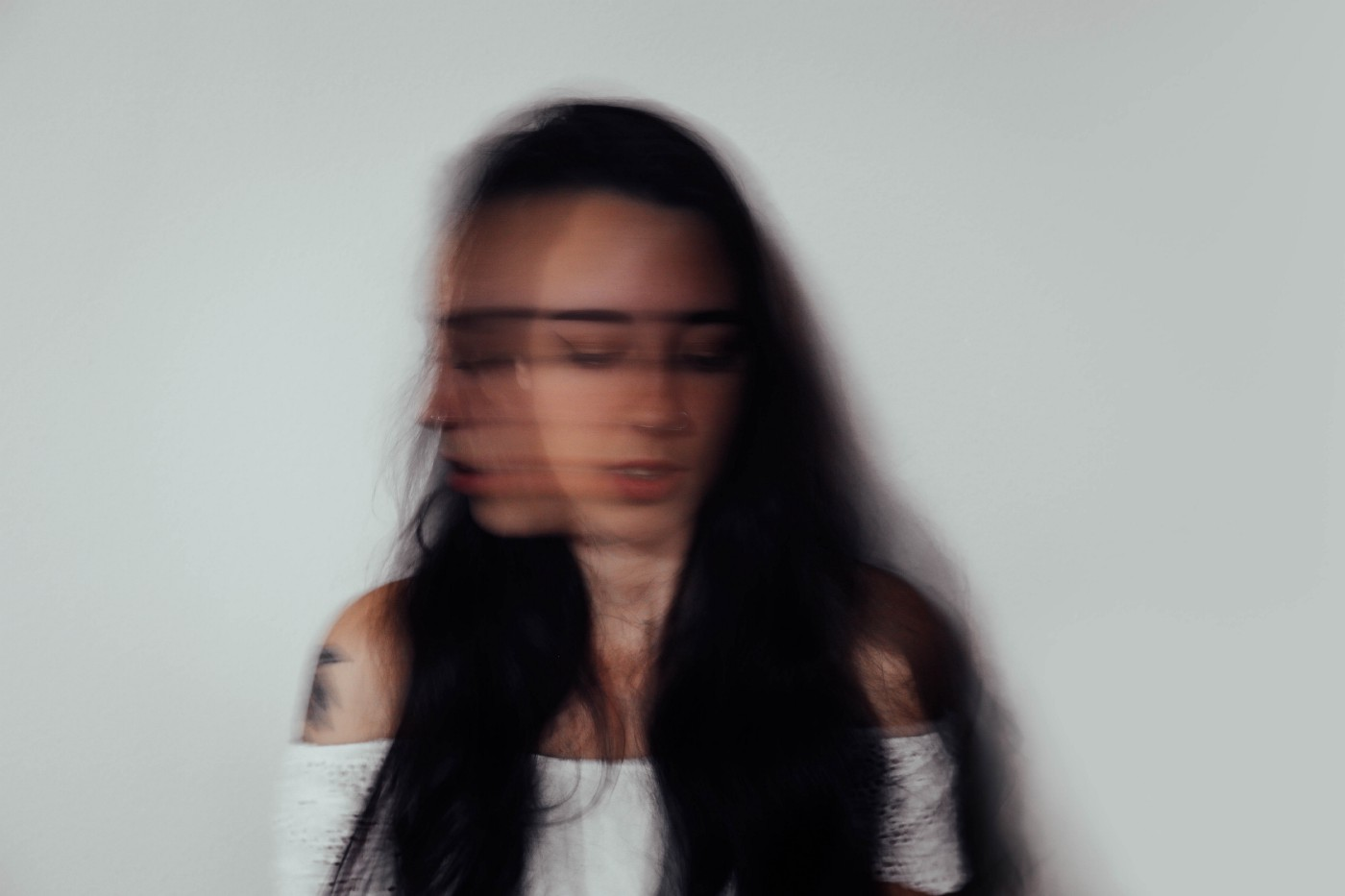This blurry image shows a woman turning her head, in which you can see different angles of her face at once.