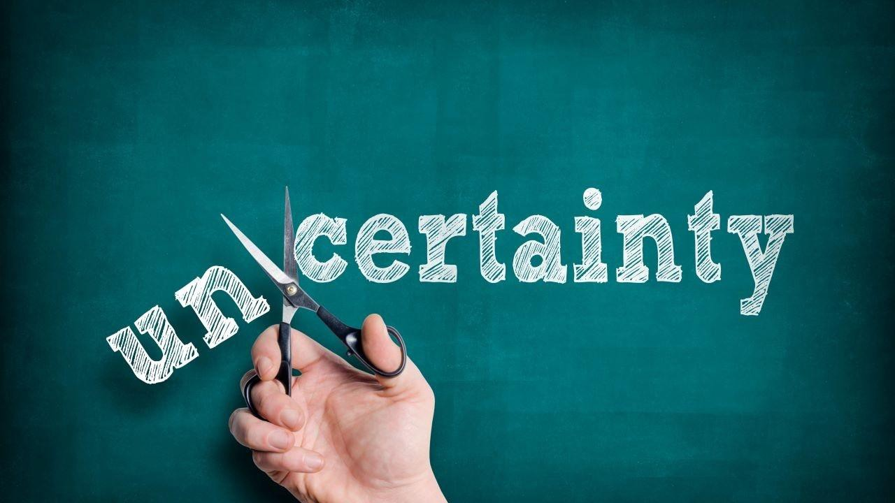 Scissors cutting the word uncertainty