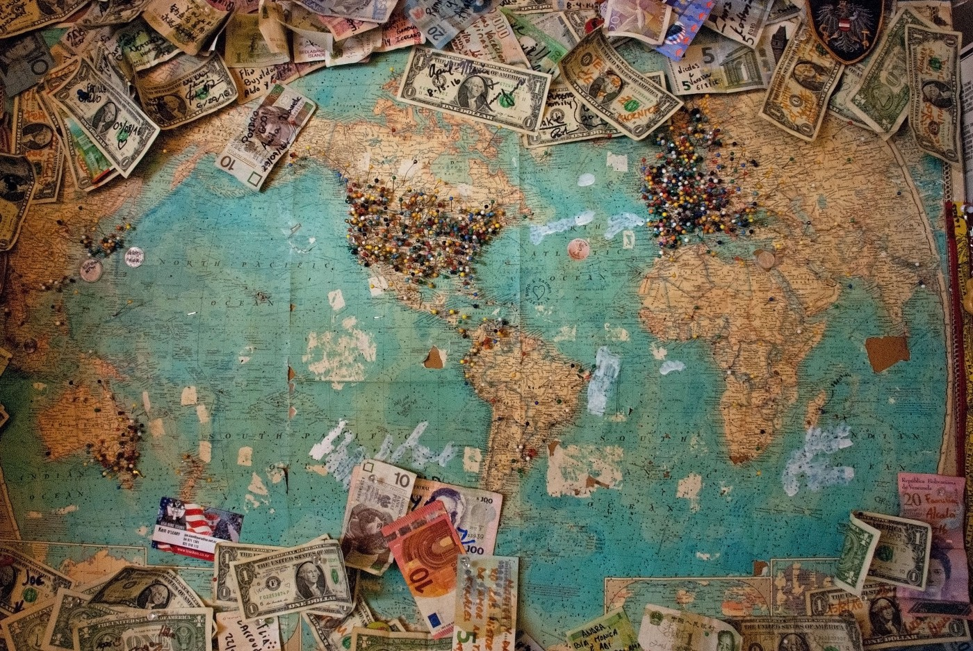 A map of the world with pins on certain places with different currencies surrounding it