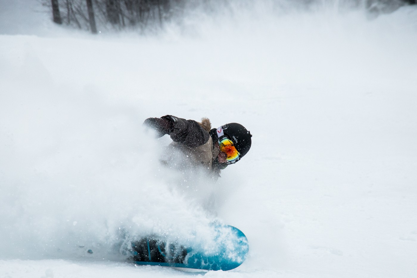 A snowboarder making a sharp cut on the mountain while kicking up snow.