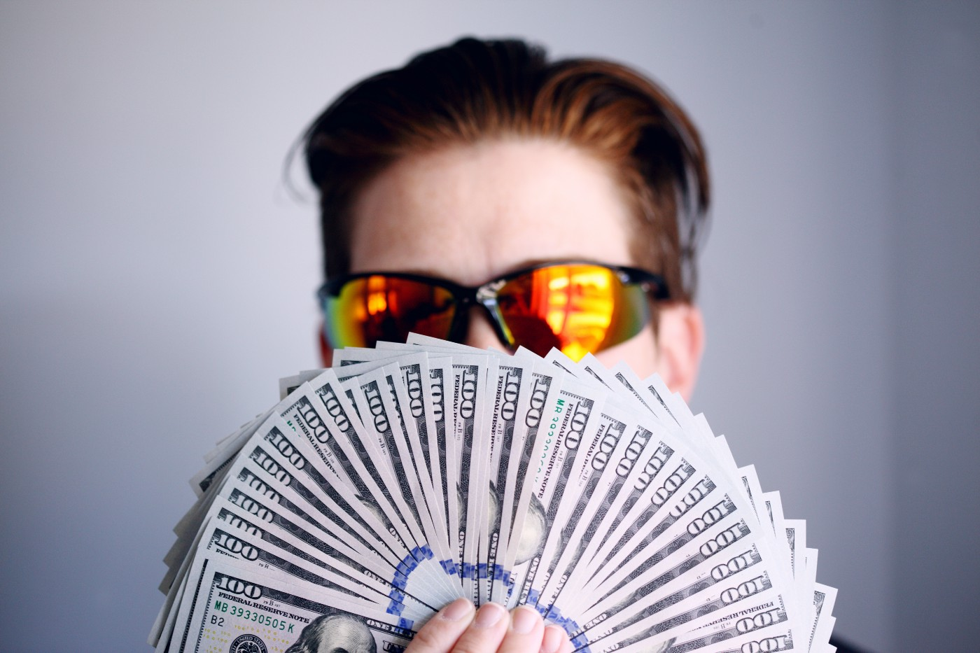 Man with glasses holds cash