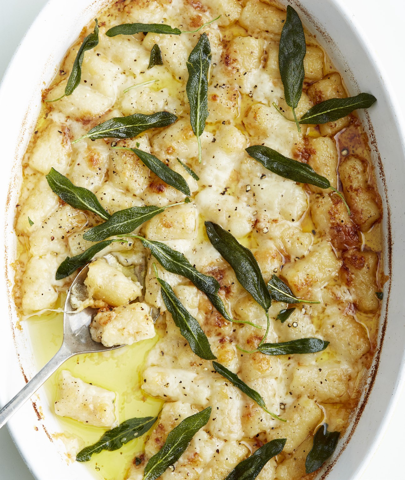An oval casserole dish of gnocchi gratin garnished with crispy sage leaves.