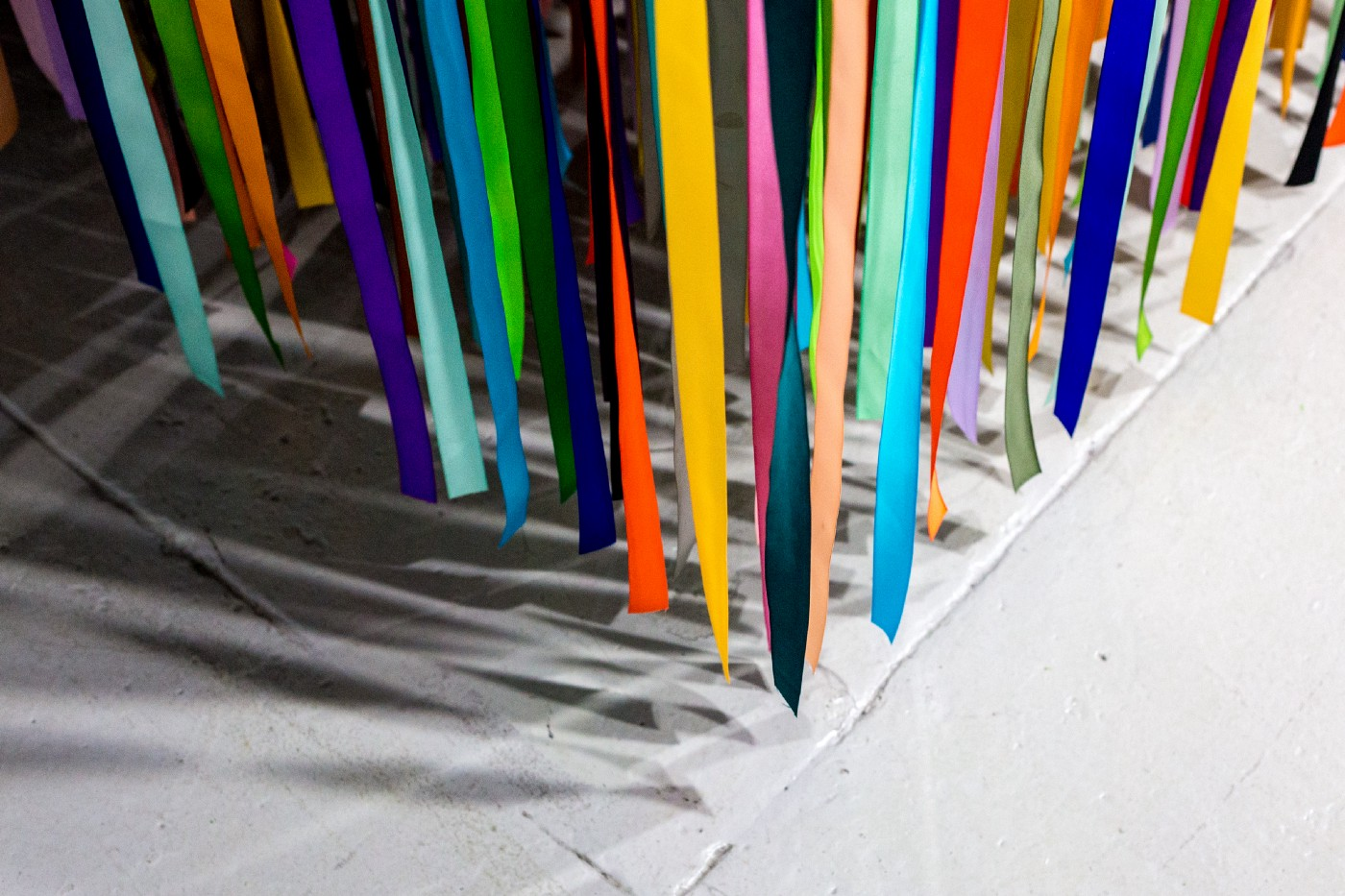 multi-colored ribbons hanging over a grey floor