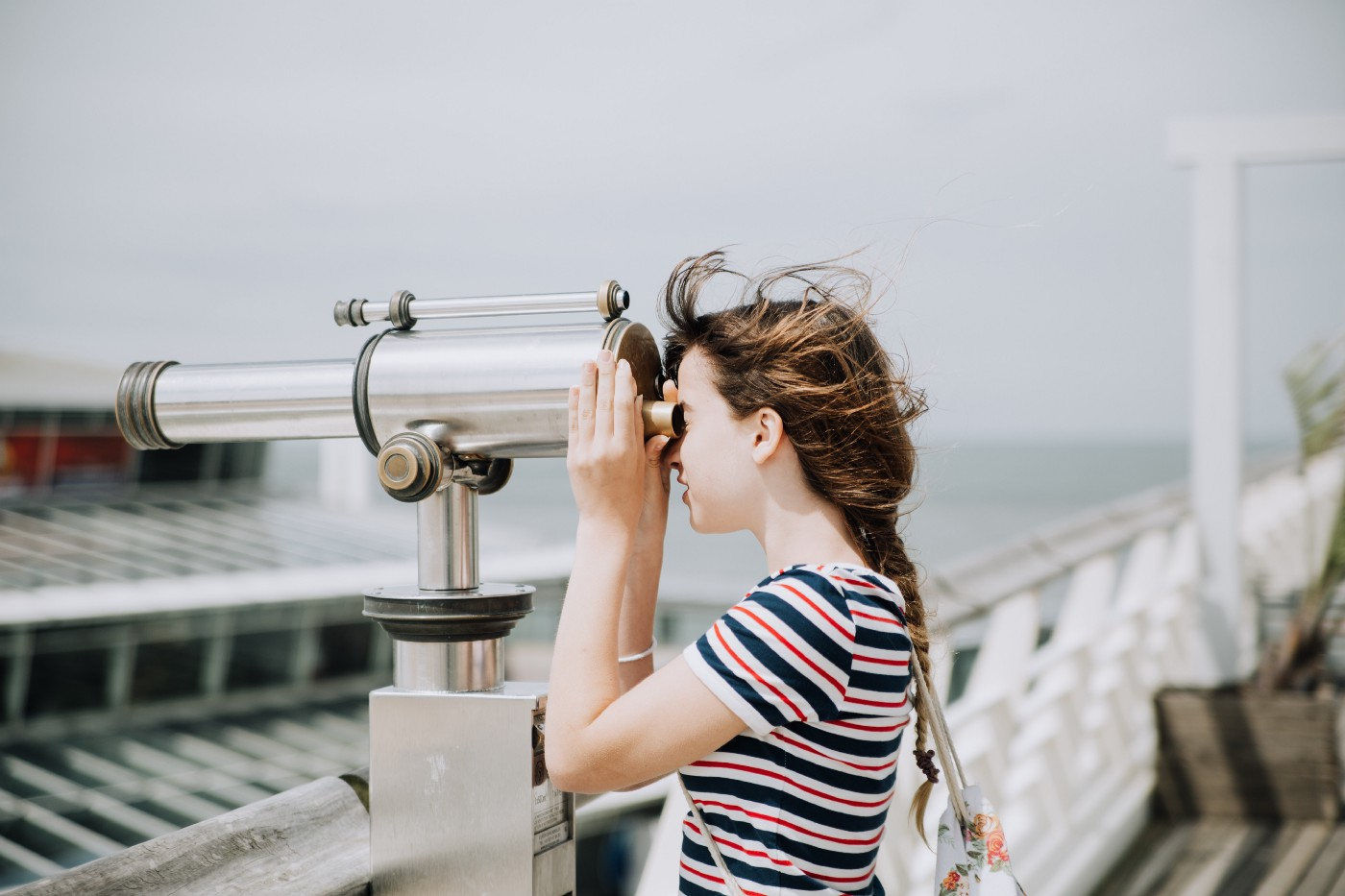 Young girl looks out to sea through binoculars on a pier