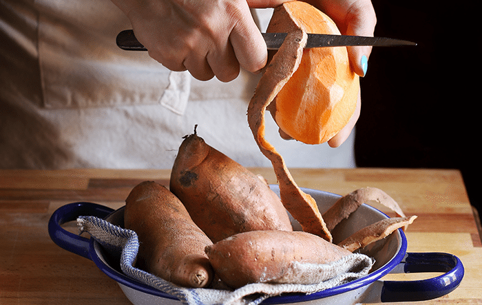 Person skinning sweet potatoes