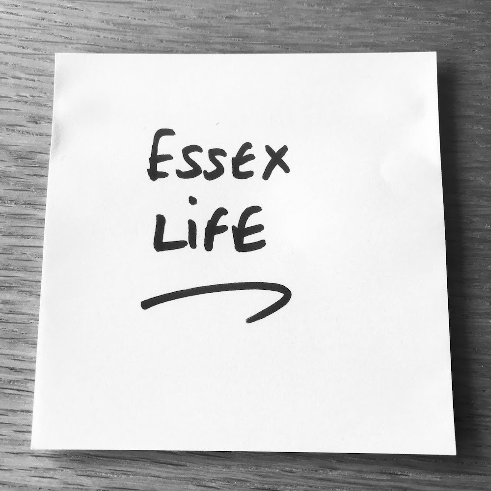 Black and white photo of a Post-It with 'Essex Life' written in black marker