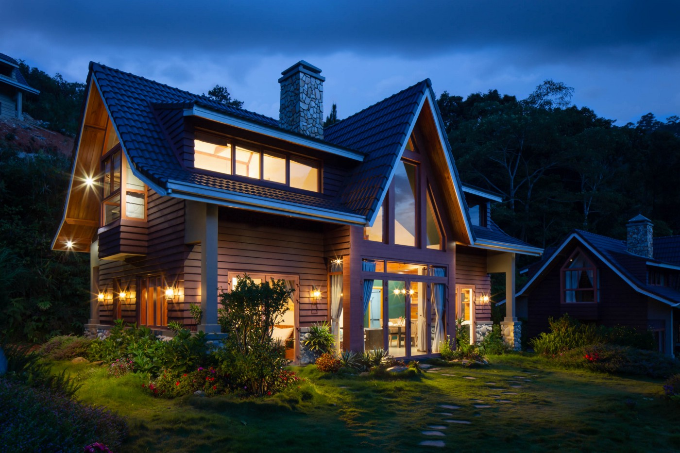Cabin-style home exterior after sunset with lights on