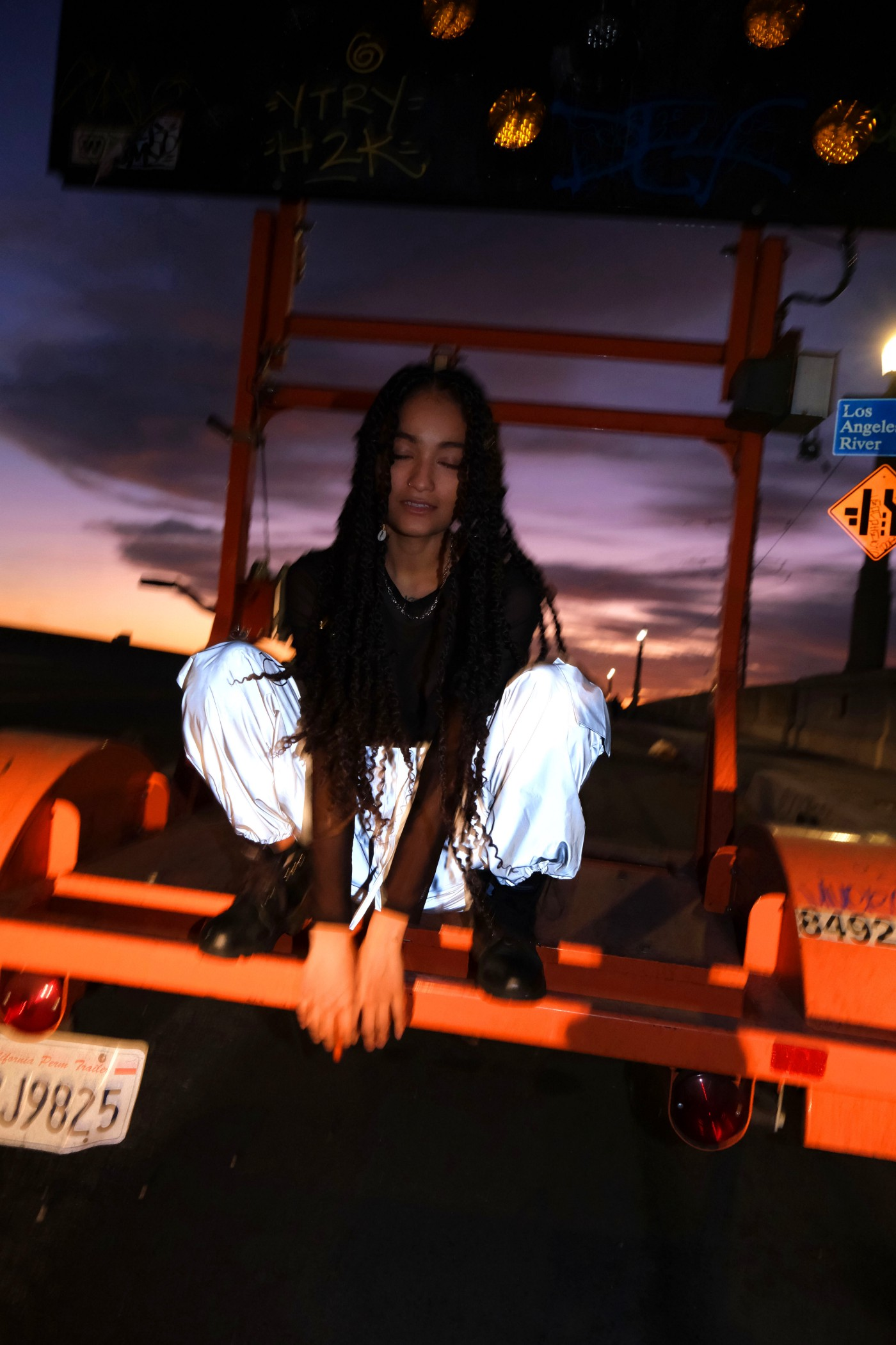 a girl with long hair in a low squat on top of what looks like the back of a trailer; her eyes are closed and she looks spaced out. She is wearing baggy jeans a long sleeved black shirt and high combat boots.