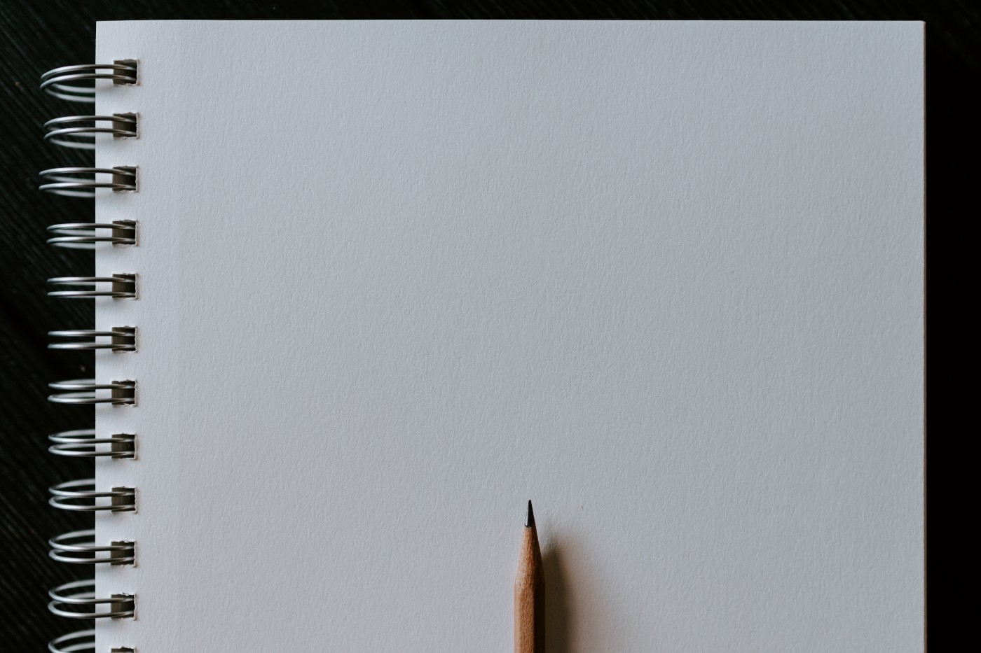 A spiral-bound notebook of white paper open to a blank page, with a sharpened wooden pencil laying atop it.