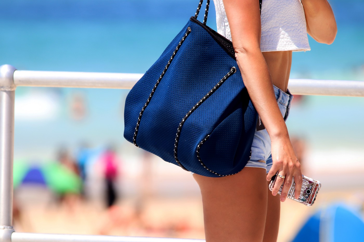 A young woman with a blue over-the-shoulder beach bag standing beside the sand of a packed beach. Crystal-blue waters are in the distance.