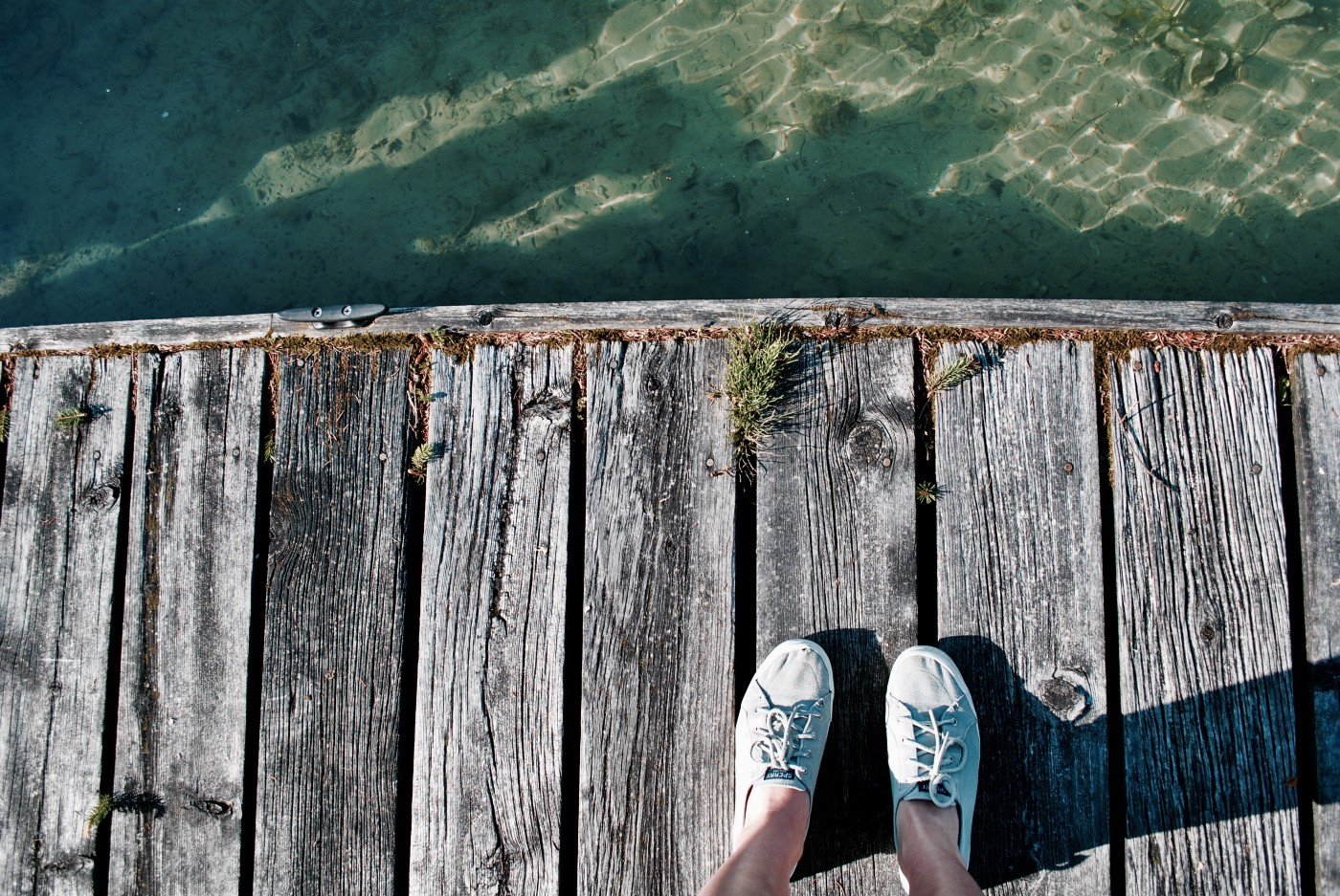 sneakered feet on a faded dock above water