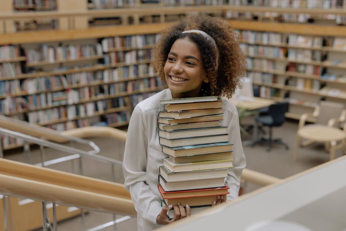 A Black woman walks up the stairs in a library or bookstore, holding a stack of books and smiling. #bookstore #library #bookrecommendations #books #booklover