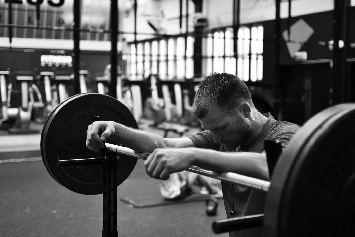 A lifter in leaning on a barbell, looking focused, in black and white.