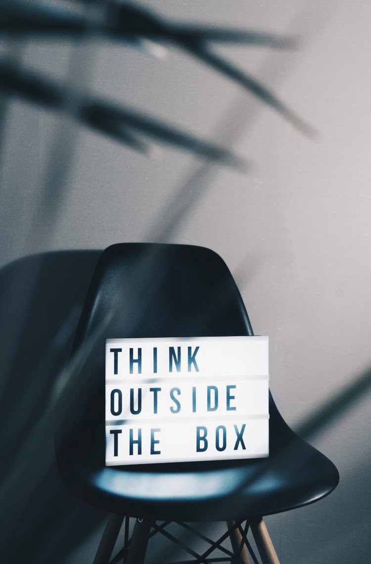 """Sign with a chair that has a note """"Think outside the box"""""""