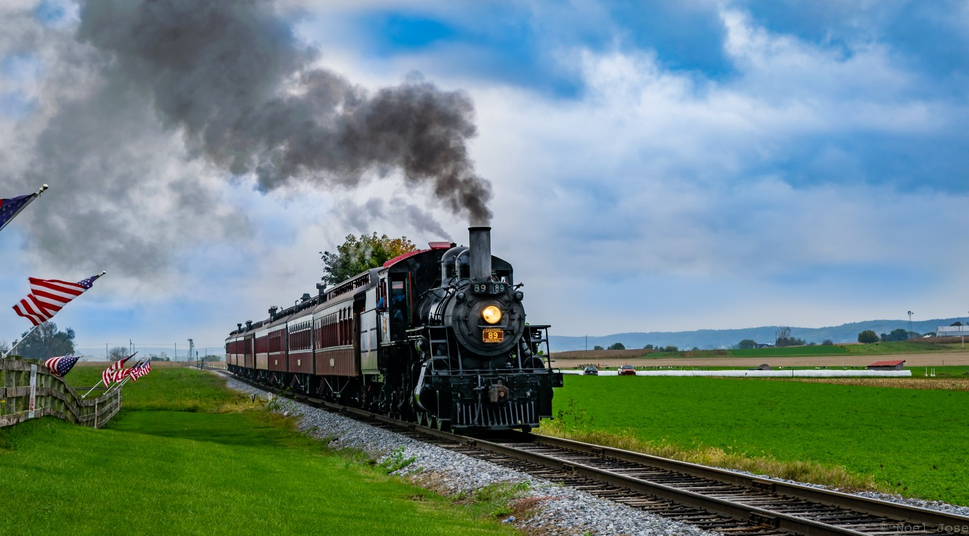 Steam engine train against blue sky and gree grass with american flags waving.