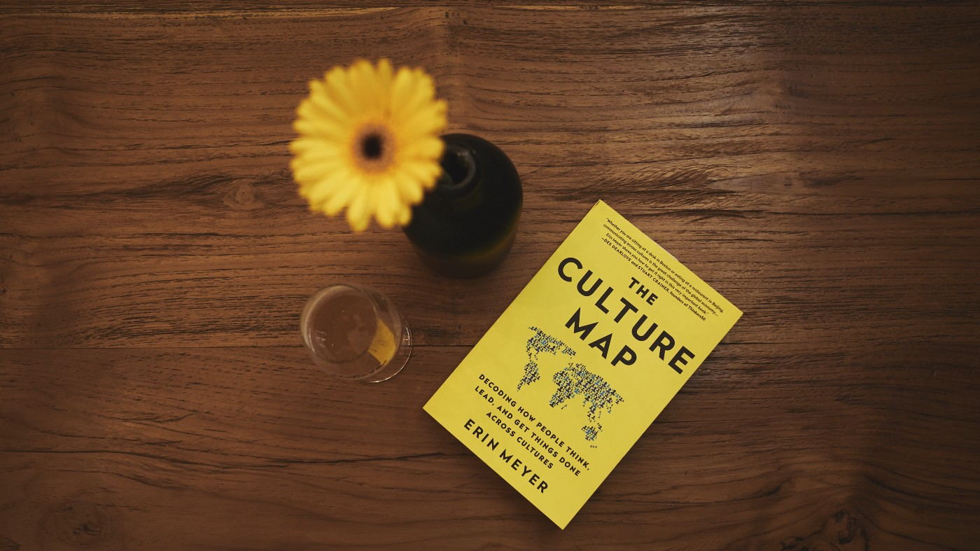"""A yellow daisy in vase next to white wine glass and yellow book titled, """"The Culture Map"""" by Erin Meyer on a brown table."""