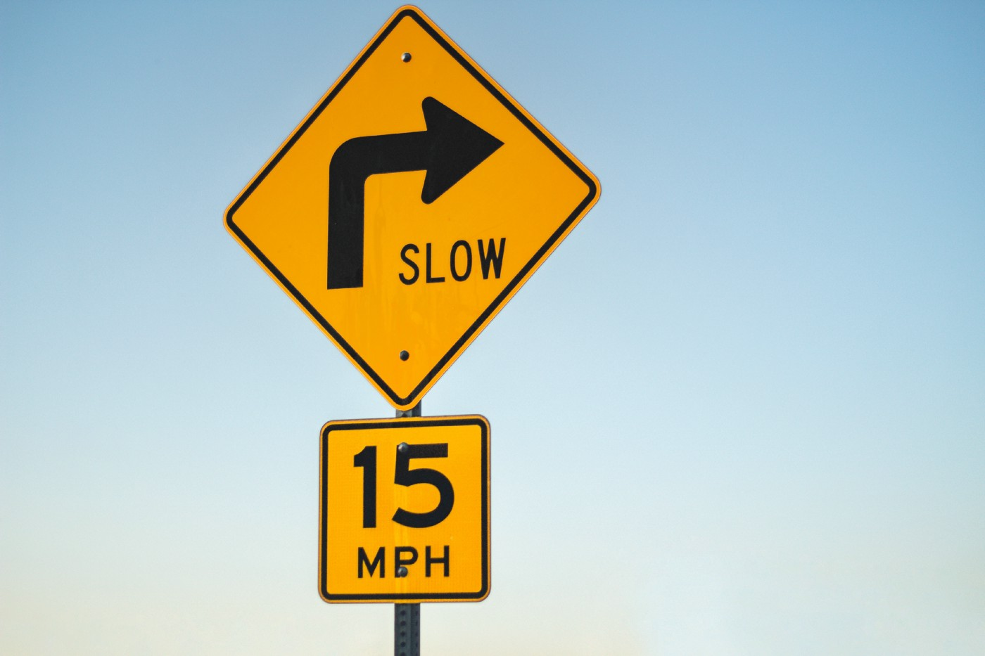 """Two road signs stacked on one another indicate a speed limit of 15 miles per hour around a corner. The only copy that accompanies the arrow icon is """"Slow"""" and """"15 MPH."""""""