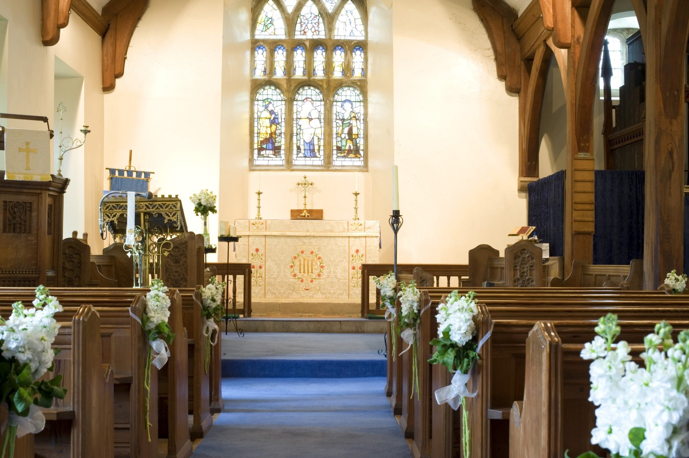 decorated church pews and altar for a wedding