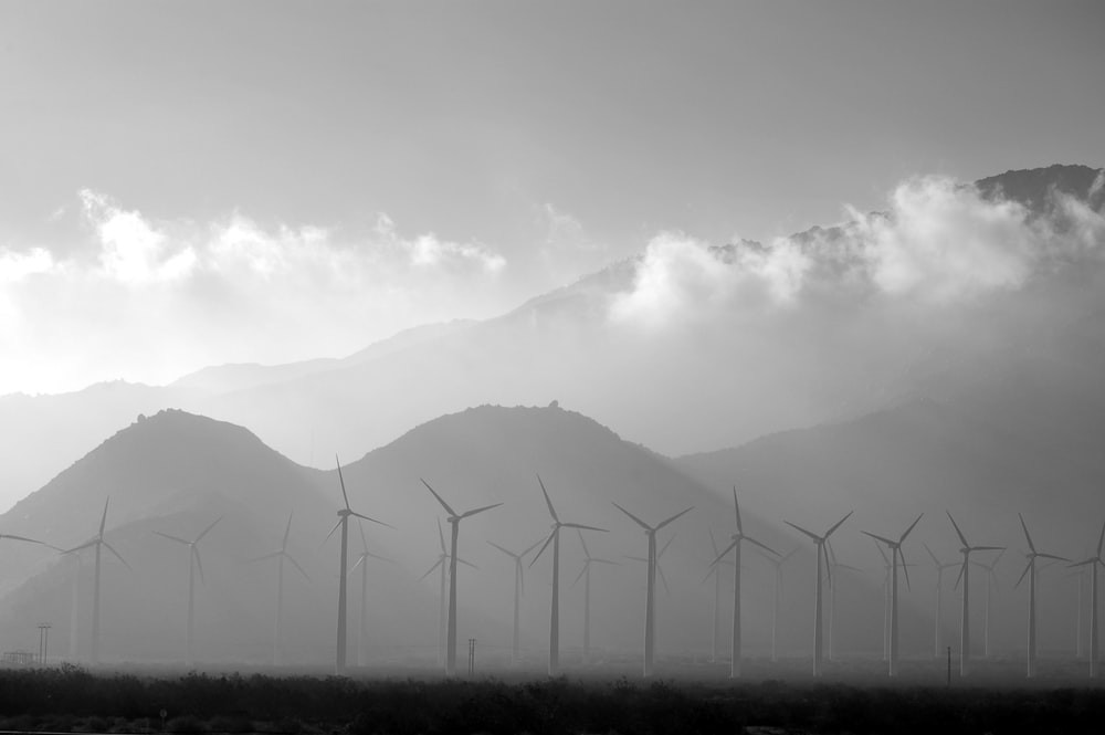 A long shot of windmills with range of mountains in the background