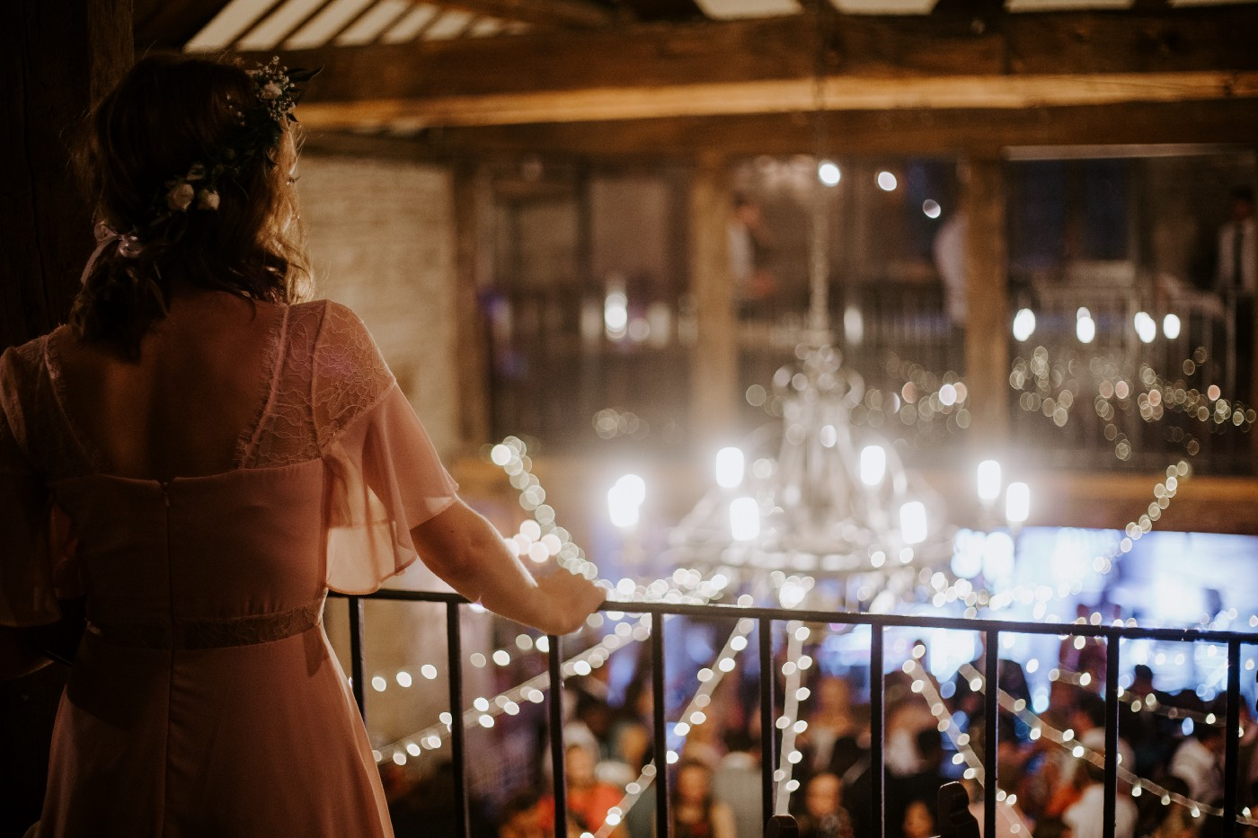 Photo of a woman in a pink dress looking over a balcony railing past fairy lights and a chandelier into a formal event.