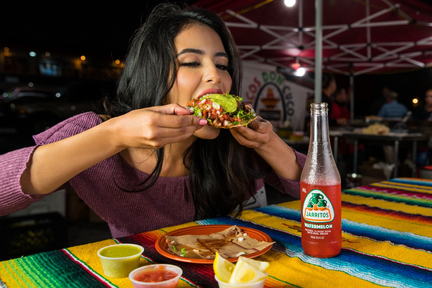 A young lady eating an overfilled taco
