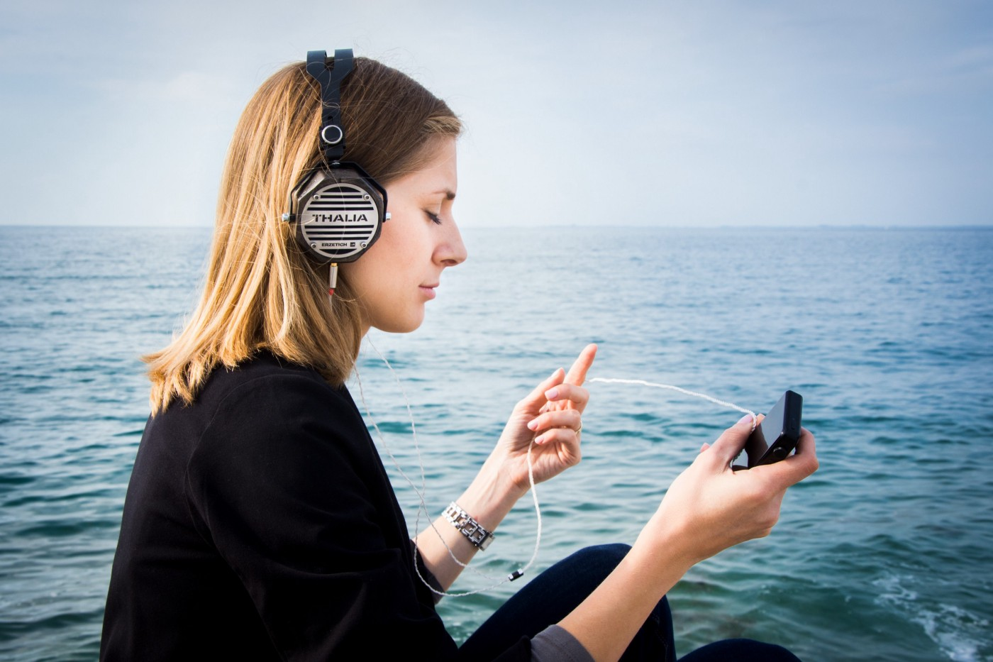 A girl listening to headphones while sitting in a body of water with a horizon and sky in the backround.