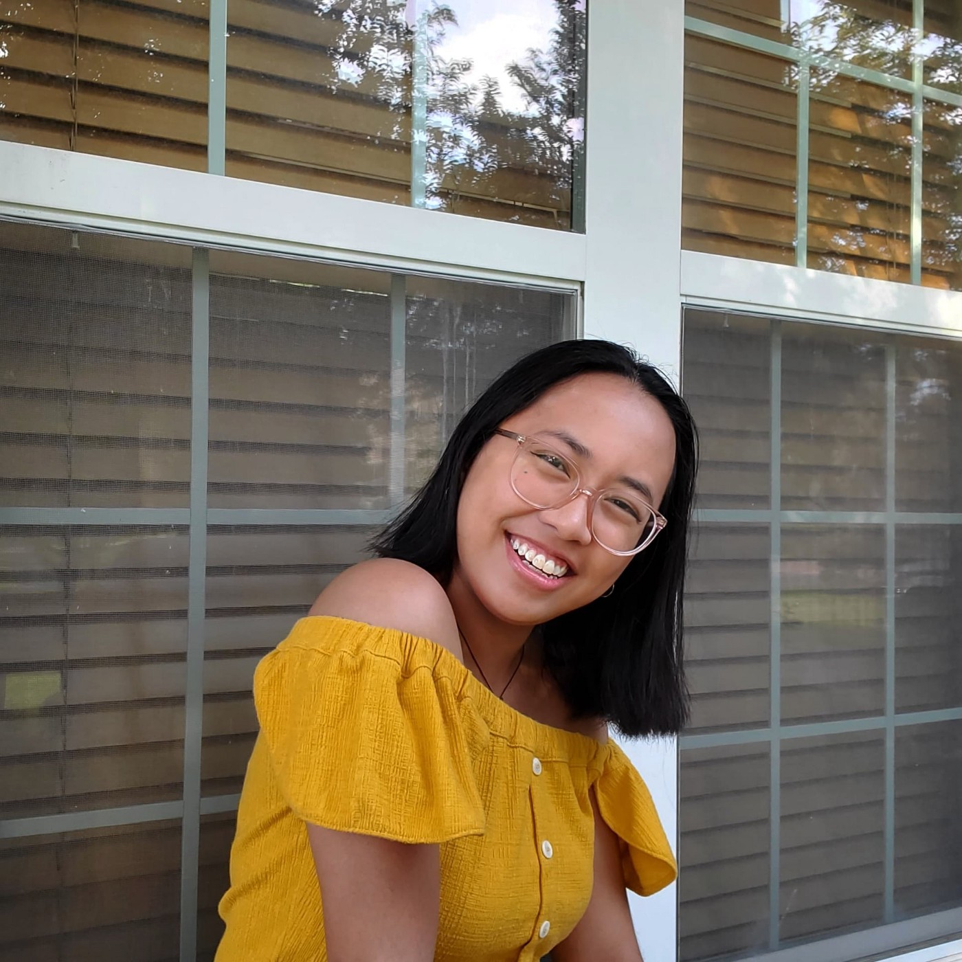 A girl in a yellow top smiles while sitting outside.