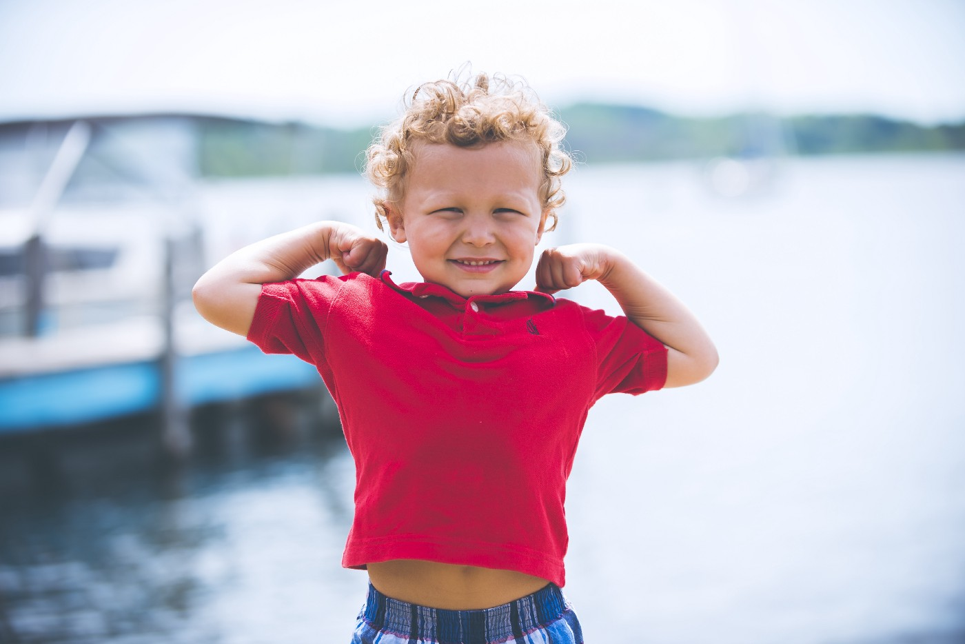 Kid flexing by the sea.
