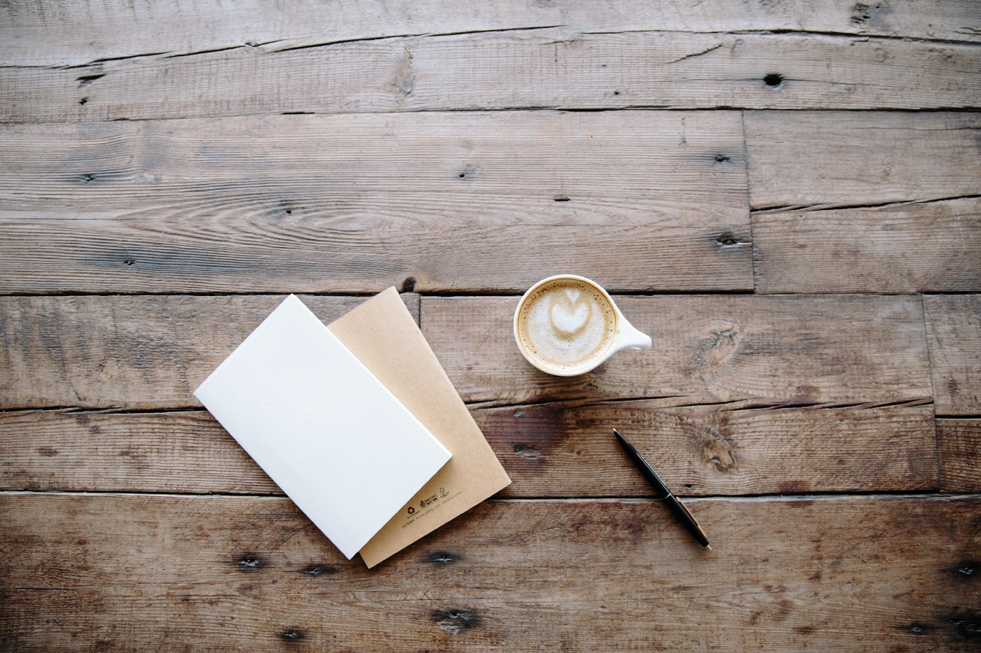 A blank sheet of paper sits next to a pen and coffee with love heart showing through froth.