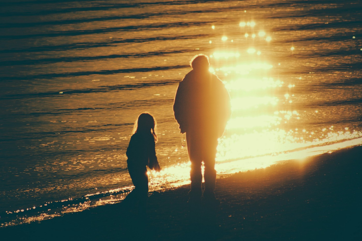 father and daughter in silhouette on beach at sunset
