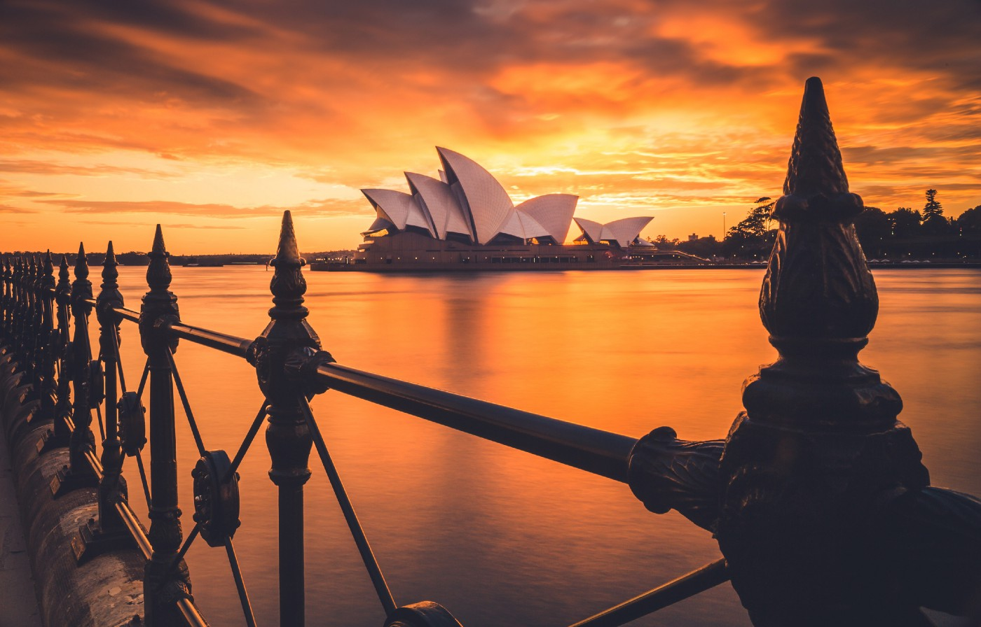 The Sydney Opera House set on a bright orange sky at dusk