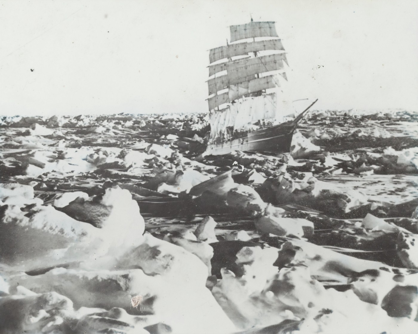 a black and white photo of a large ship sailing amidst the frozen ice caps in the ocean