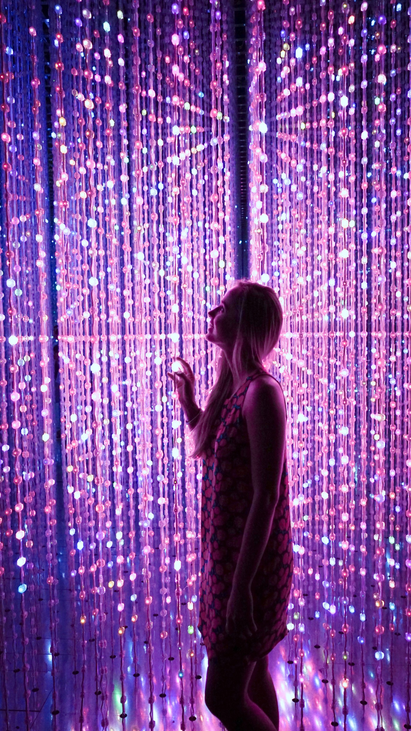 Smiling girl in a room that sparkles with gentle purple light.