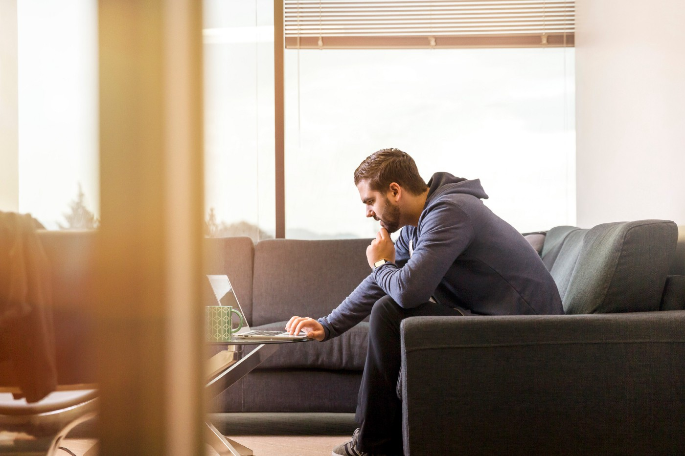 man curled forward using a laptop