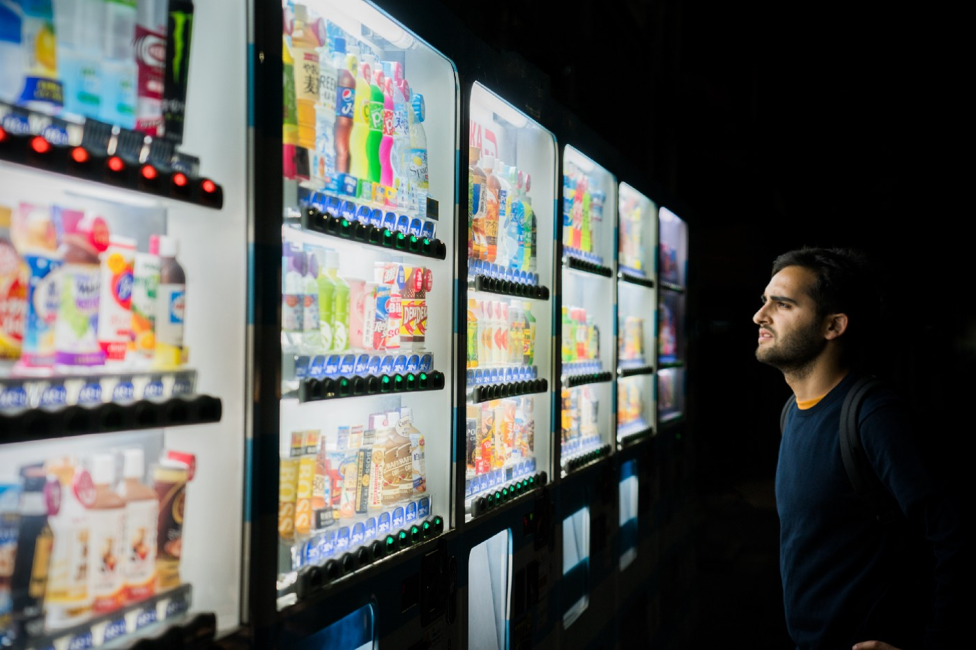An image of a Human looking at a six panel wide vending machine and looking confused about what choice to make.