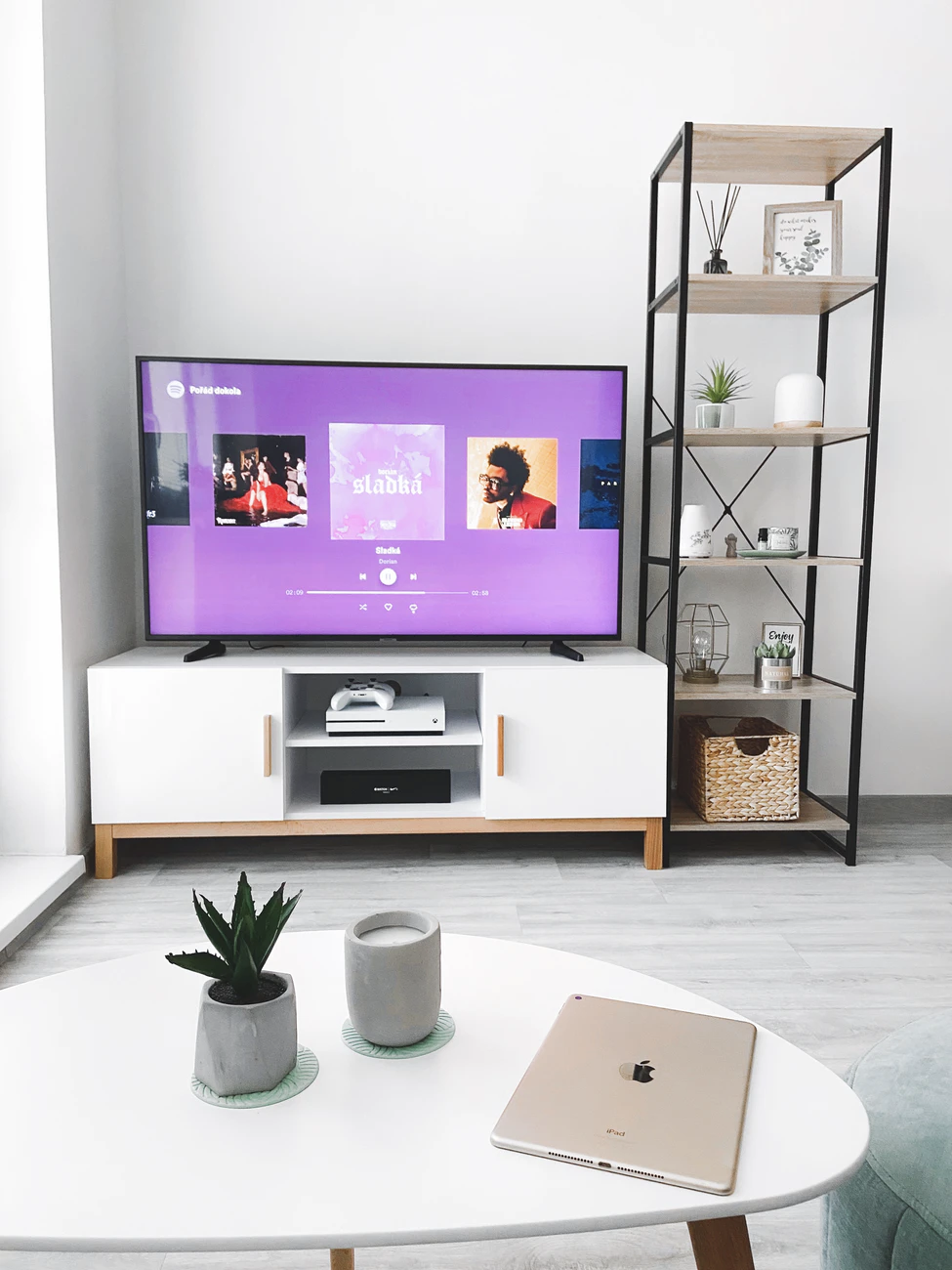 TV on white entertainment stand turned on to the Spotify music app.