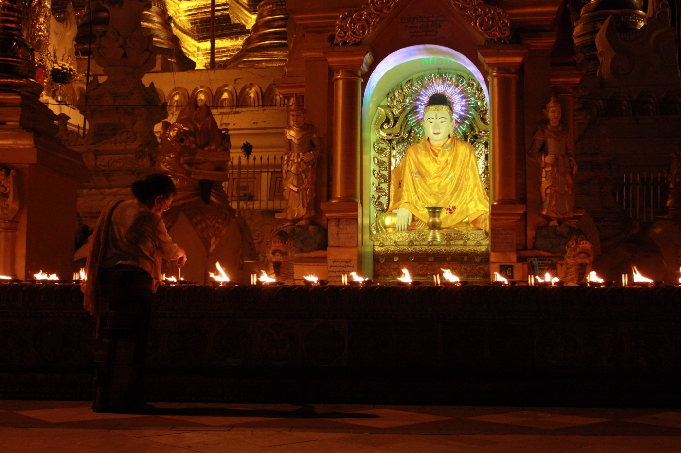 An image of a buddha statue surrounded by lights, a person lights a candle.