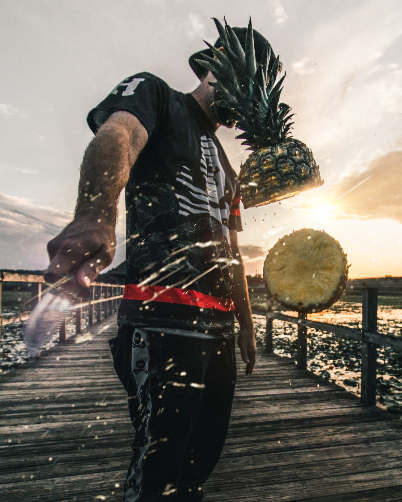 Man on dock at sunset slices pineapple with knife