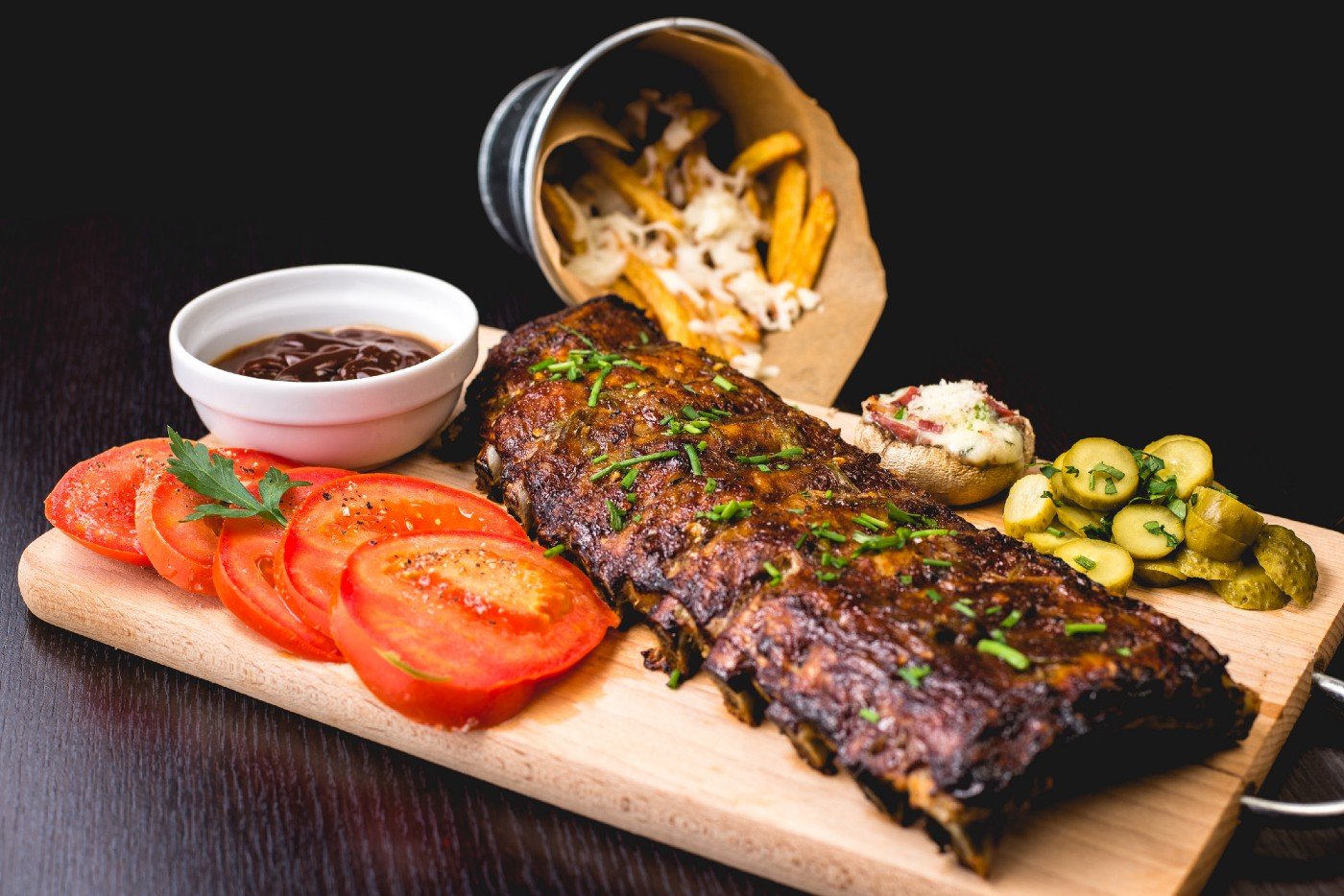 Beef ribs with piles of chopped tomato, gravy and fries in a bucket.